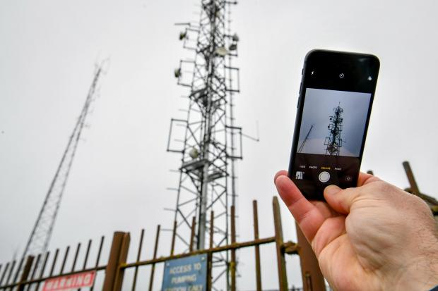 A mobile phone next to a telecoms mast
