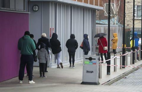 People queue at The Centre in Slough, Berkshire, after a rapid testing hub was opened for local residents during England's third national lockdown to curb the spread of coronavirus (PA)