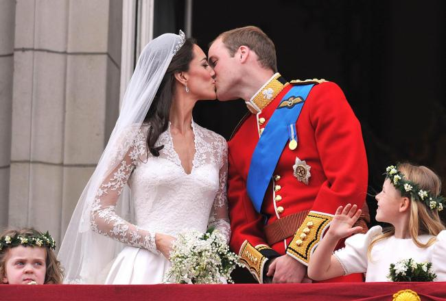 Prince William and his wife Kate Middleton kissing on the balcony of Buckingham Palace, London, following their wedding at Westminster Abbey. Credit: PA Wire