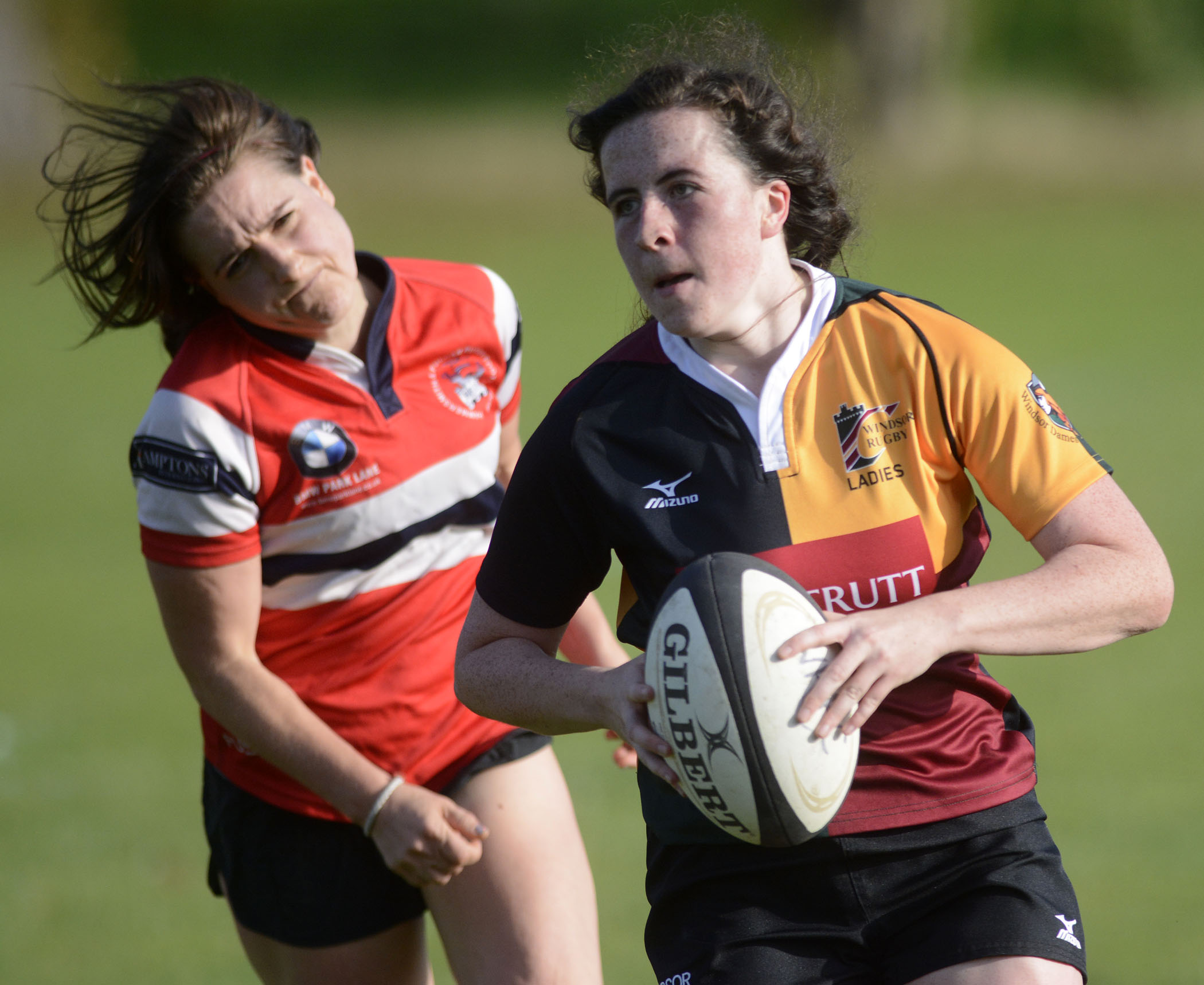 Windsor Dames (yellow and black) double try scorer Molly Horler sprints away from a chasing defender.